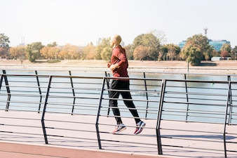 健康を維持するために屋外で走る男性アスリートにフィット