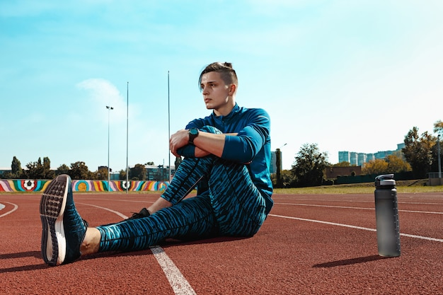 The fit male runner stretching legs preparing for run during training at stadium tracks. the athlete, fitness, workout, sport, exercise, training, athletic, lifestyle concept