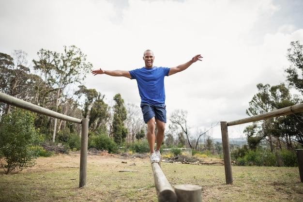 Подходящий мужчина балансирует на препятствиях во время тренировки по полосе препятствий в учебном лагере
