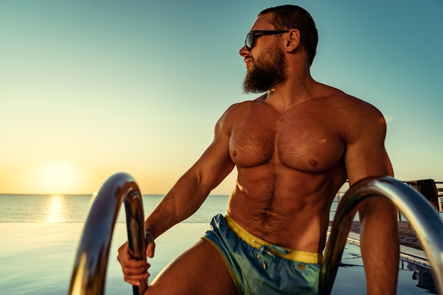 Fit man bodybuilder coming out of pool