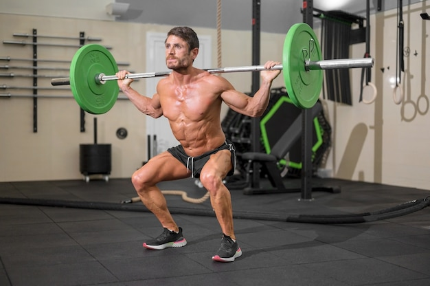 Fit man bodybuilder doing barbell squats at gym Premium Photo