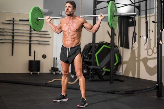 Fit man bodybuilder doing barbell squats at gym