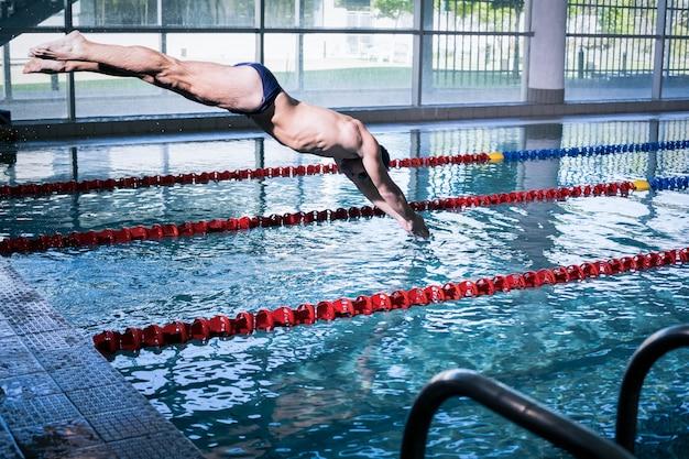 Fit человек, ныряющий в бассейн