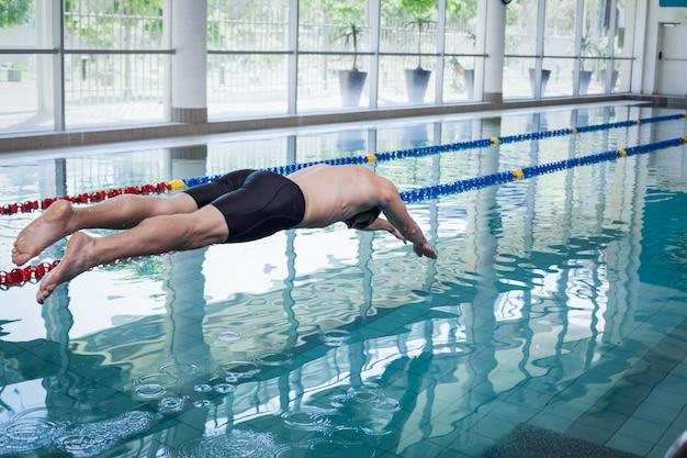 Подходит мужчина, ныряющий в воду у бассейна