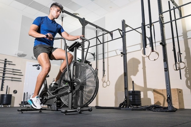 Fit man doing cardio training on stationary air bike machine with fan at the gym
