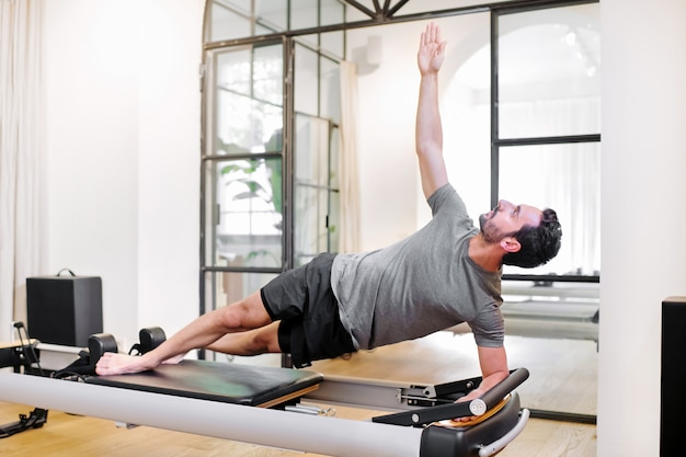 Fit man doing pilates side elbow plank exercises