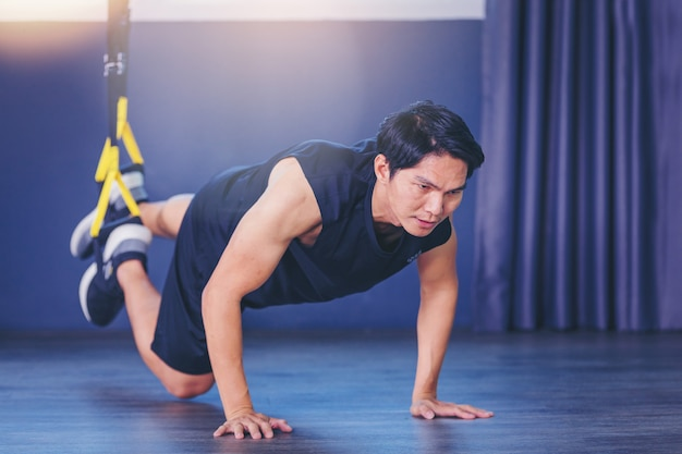 Fit man doing plank exercise for back spine by push ups with rope fitness straps in the gym