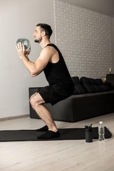 Подходит мужчина, делающий приседания с большой бутылкой воды в руках дома. квартира с минималистичным интерьером на заднем плане. черная спортивная одежда. концепция здорового образа жизни, благополучия и деятельности.