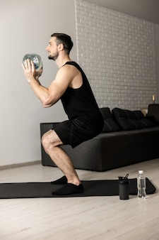 Fit man doing squat exercises with big bottle of water in hands at home. apartment with minimalistic interior on background. black sportswear. healthy lifestyle, wellbeing and activity concept.