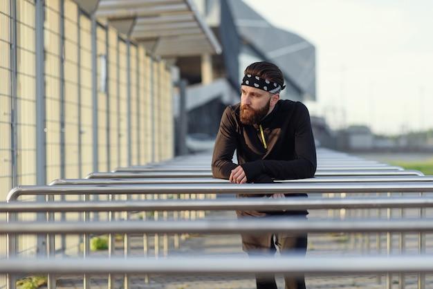 Подходящий мужчина делает отжимания на трицепс на брусьях в парке, тренируясь на открытом воздухе