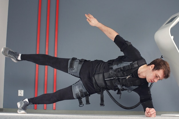 Fit man in electrical muscular stimulation suits doing side plank exercise.