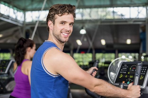 Fit man on elliptical bike at gym