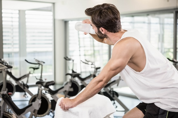 Fit man on exercise bike drinking water at the gym