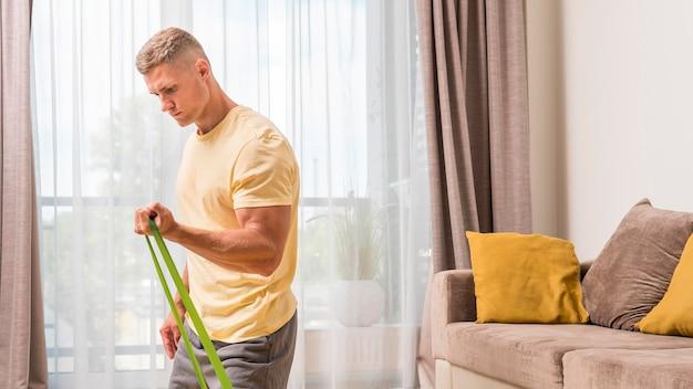 Подходит мужчина, тренирующийся дома, с помощью резинки