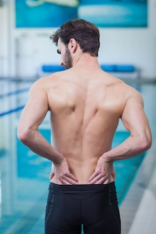 Fit man having back pain at the pool