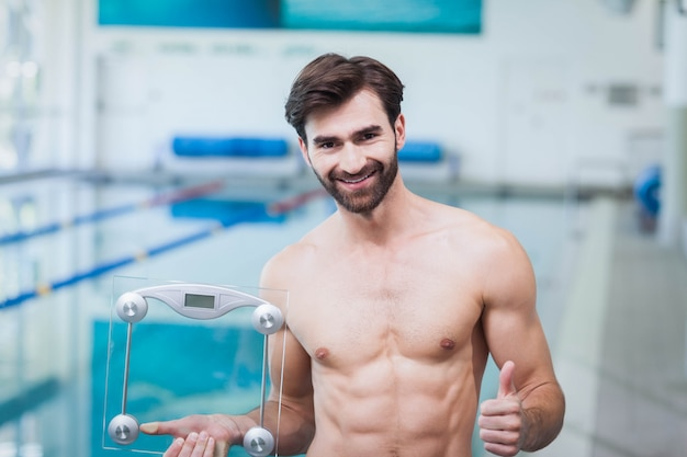 Fit man holding a weighting scale with thumbs up at the pool