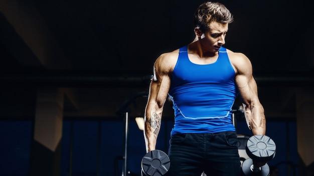 ジムで青い袖なしのトップトレーニング腕の筋肉に男を合わせる