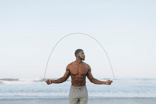 ぴったりの男性がビーチで縄跳び