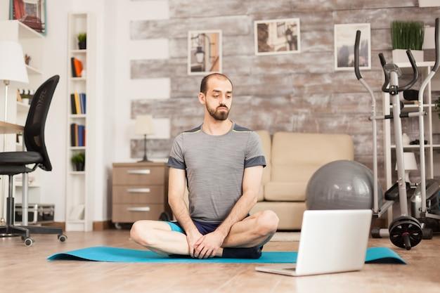 Подходящий мужчина изучает йогу из онлайн-курса во время глобальной пандемии.