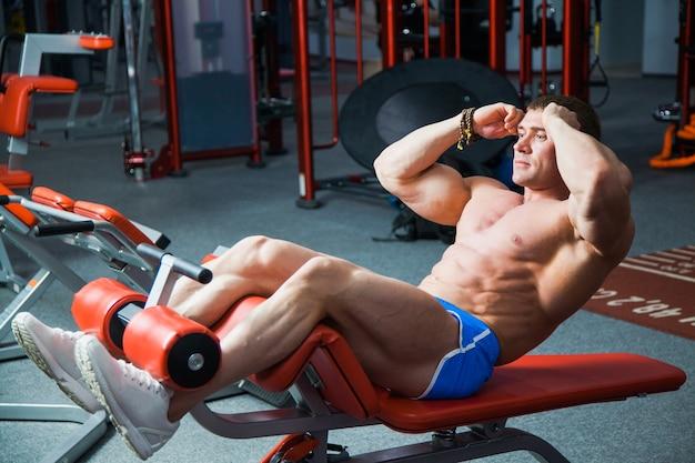 맞는 남자 리프트 몸통은 체육관에서 복부 근육 운동을 훈련합니다. 젊은 보디 빌더는 스포츠 장비로 복근 운동을합니다.