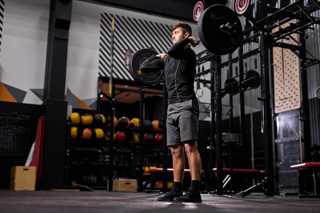 Fit man lifting barbell in crossfit gym, bodybuilding and weightlifting concept. male in sportswear engaged in cross fit workout, training alone