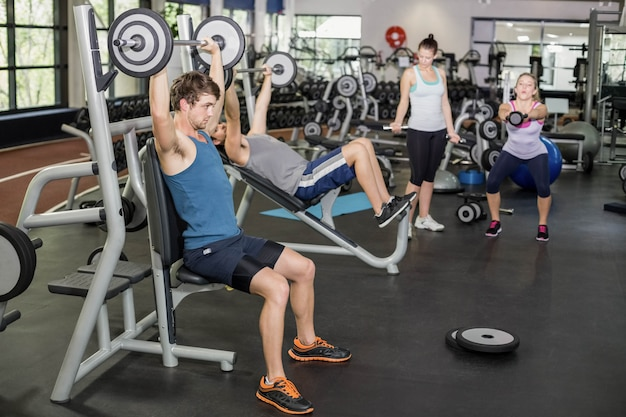 Fit man lifting barbell at crossfit gym