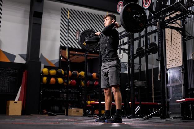 クロスフィットジム、ボディービル、重量挙げのコンセプトでバーベルを持ち上げる男性にフィットします。クロスフィットトレーニングに従事しているスポーツウェアの男性、一人でトレーニング