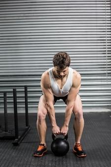 Fit man lifting dumbbells at crossfit gym