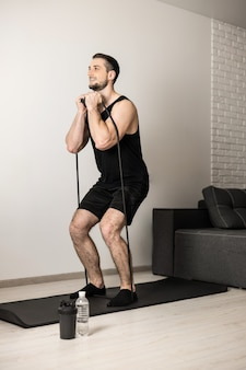 Fit man performs exercises using a resistance band. hard workout at home. minimalistic interior on background. water bottle near yoga mat. a man gets pleasure from doing his favorite exercise.