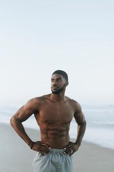 ぴったりの男性がビーチでポーズ