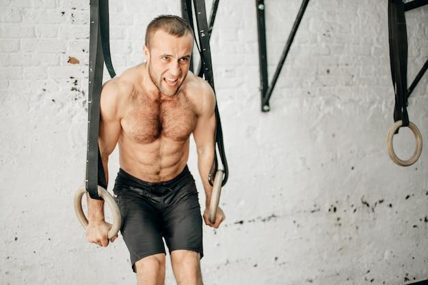 体操リングを引き上げてフィット男。