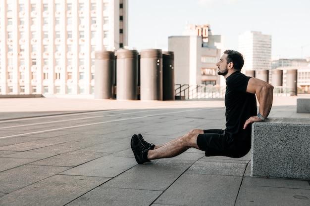 돌 큐브에서 밀어 맞는 남자. 아침 운동 야외. 검은색 운동복. 그의 팔을 강화하기 위해 열심히 연습하는 남자. 도시 스포츠 개념입니다. 아침 피트니스. 배경에 도시입니다.