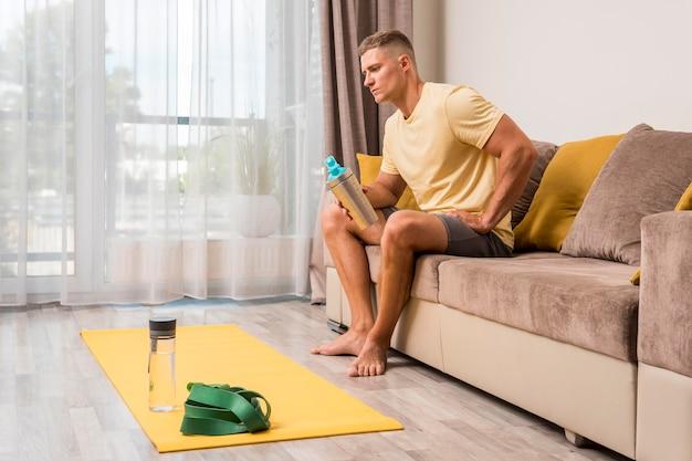 Подходит мужчина, расслабляющий на диване после тренировки