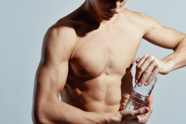 Fit man torso with a bottle of water