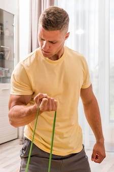Fit man training at home using elastic band
