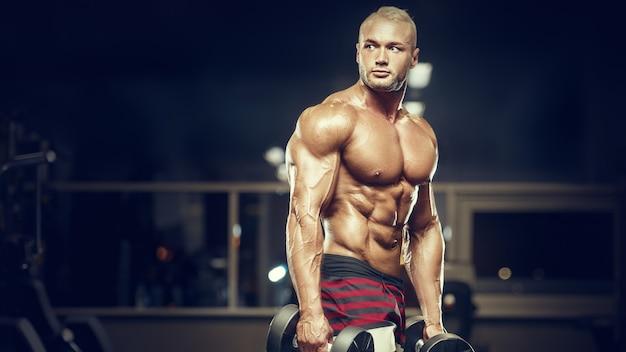 체육관에서 남자 훈련 근육을 맞추십시오. 운동시 근육을 닫습니다. 보디 빌딩, 피트니스 및 건강 관리 개념.