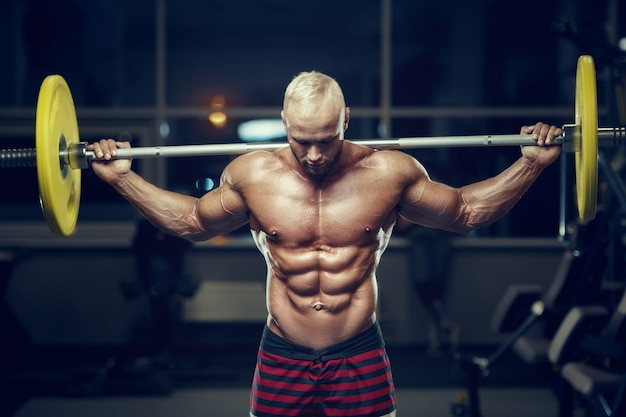 Fit man training muscles at gym. close up muscles at workout. bodybuilding, fitness and health care concept.