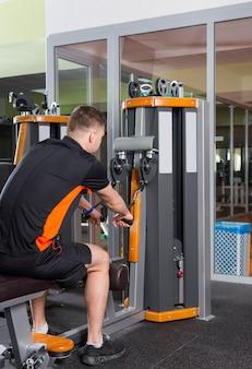 フィットネスセンターのジムルームのローイングマシンでトレーニングする男性