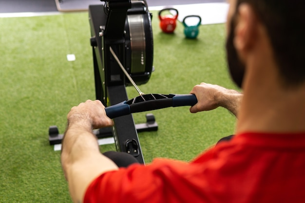 ジムのローイングマシンでトレーニングする男性にフィット
