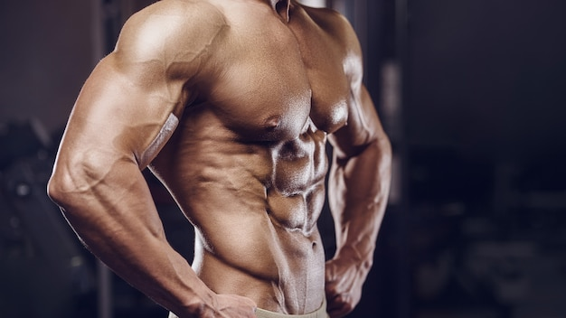 Fit man training training abs muscles at gym. pumping up abdominal exercise.