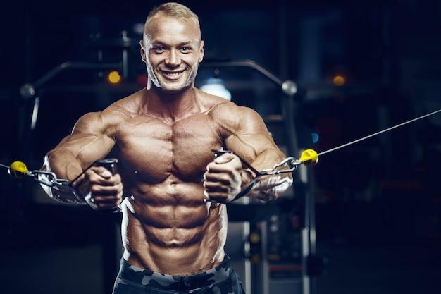 체육관에서 남자 훈련 훈련 팔 근육을 맞추십시오. 팔뚝 운동을 펌핑.