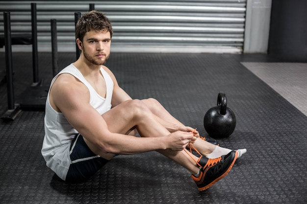 Fit man tying up her shoe laces at crossfit gym