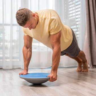 Fit man using bosu ball to exercise at home