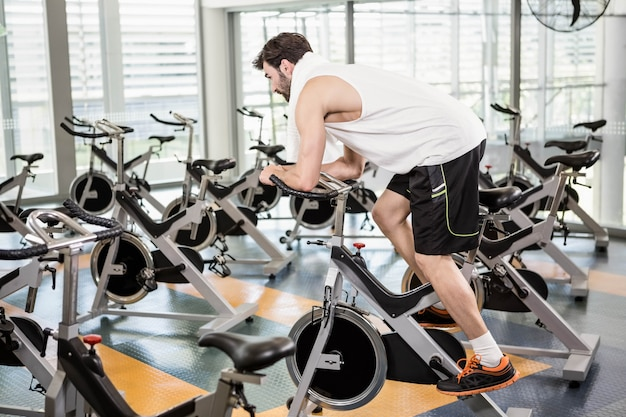 Fit man using exercise bike at the gym