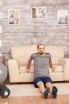 コロナウイルスの封鎖中に上腕三頭筋を訓練するためにソファを使用して男性にフィットします。