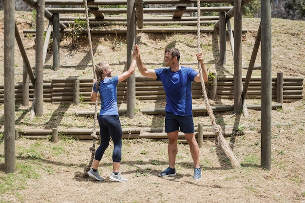 Fit man and woman giving high-five to each other during obstacle course in boot camp