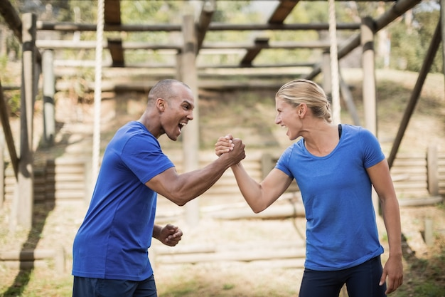 Fit man and woman greeting each other during obstacle course in boot camp