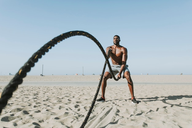 Fit man working out with battle ropes