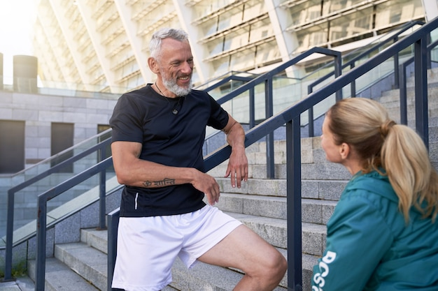 Fit mature couple chatting while standing outdoors after morning workout in the city