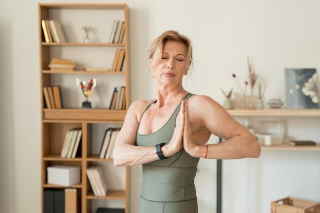 Подходит для зрелой женщины в спортивной одежде, держа руки вместе грудью, делая упражнения йоги на досуге в домашней обстановке